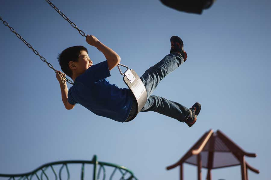 An image of a child without anxiety playing on a swing in Toowong.