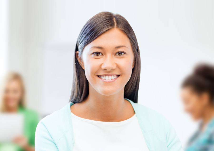 An image of a woman at her workplace smiling after workplace counselling therapy.