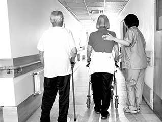 An image of a couple in a rehabilitation hospital with an attendant.