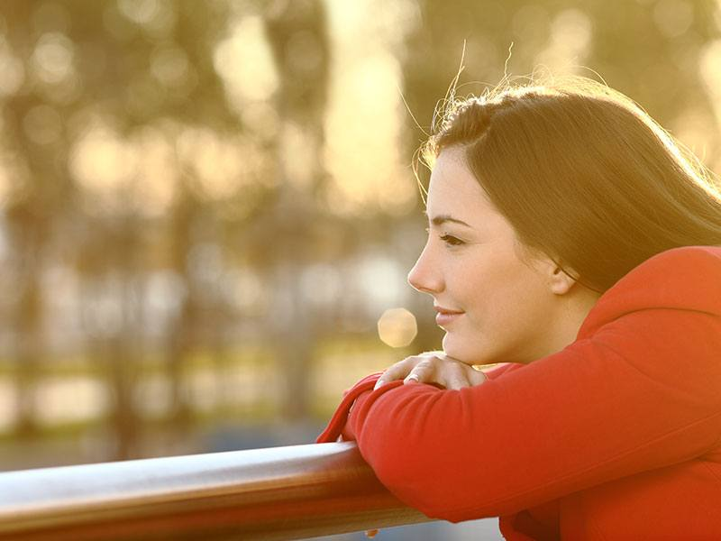 An image of a woman thinking while relaxing in the balcony, she is stress free and emotionally independent.