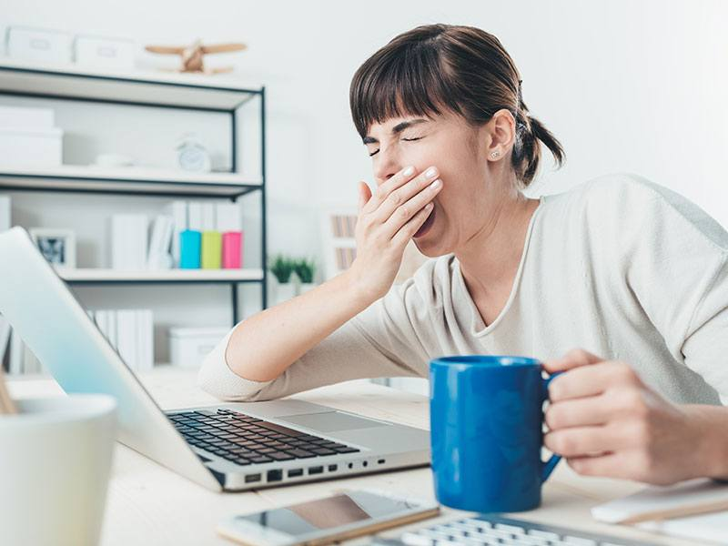 An image of a woman yawning while facing her laptop and drinking coffee suffering from sleep issues.