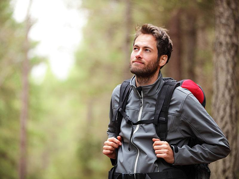 An image of a man walking in the forest for a hike with a backpack clearly mentally healthy.